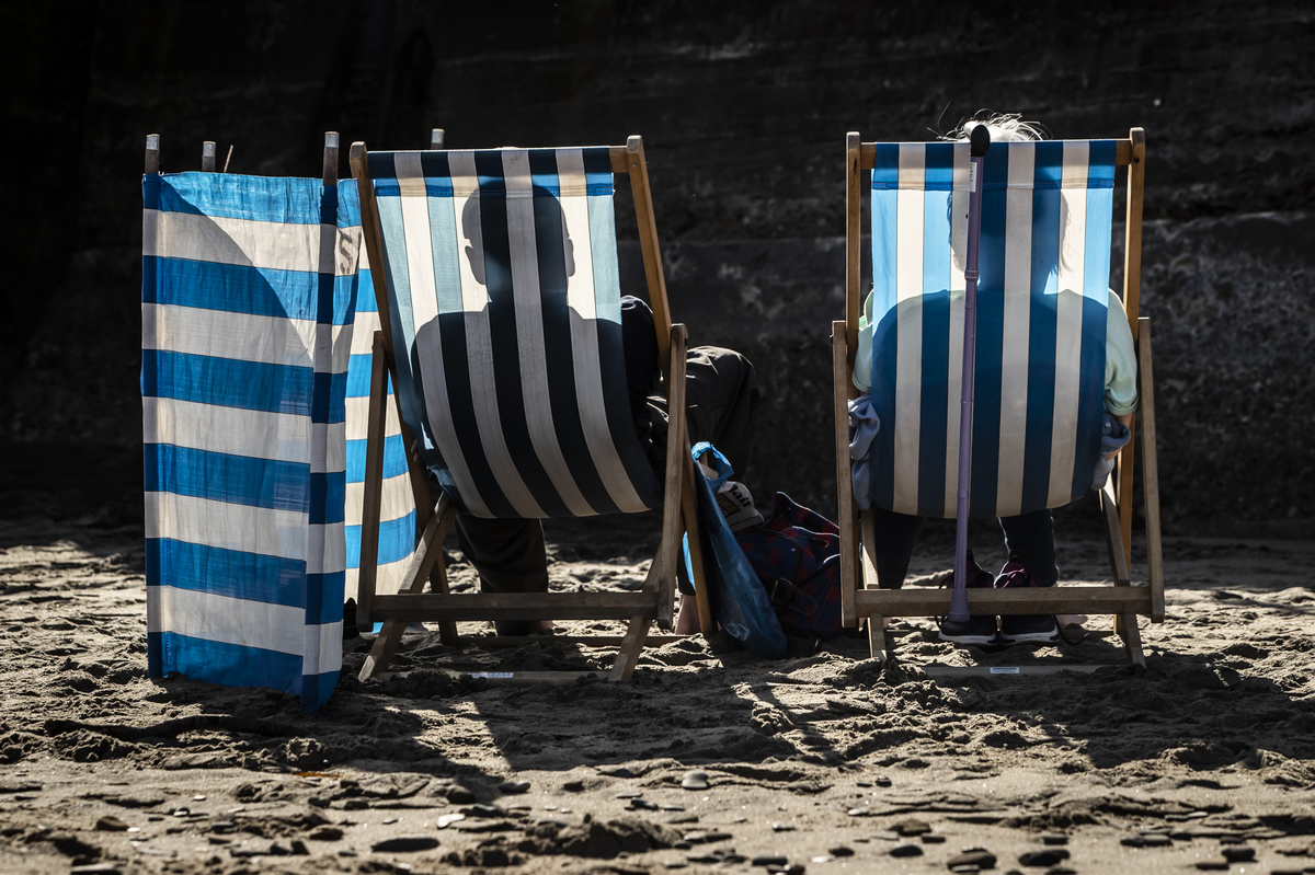 two people sitting in blue and white striped beach chairs