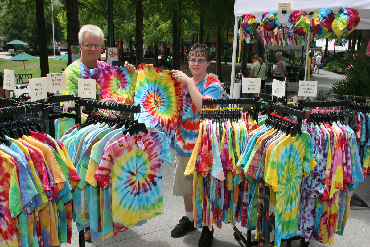 A father and son selling tie dye shirts at the Farmers Market at Heritage Park.