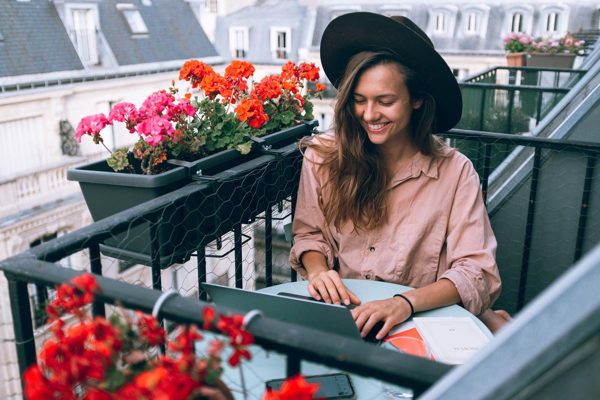 woman smiling at laptop sitting outside on balcony