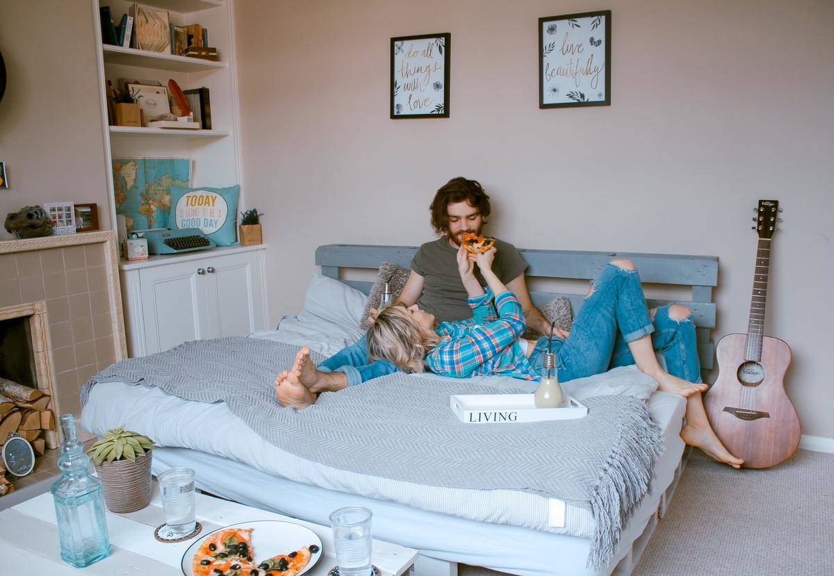 man and woman eating pizza in bed