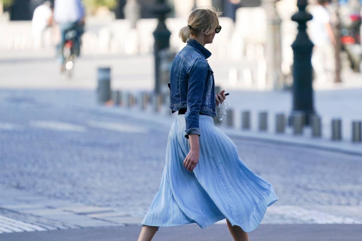 A passerby wears a blue denim jacket, a pale blue pleated flowing skirt