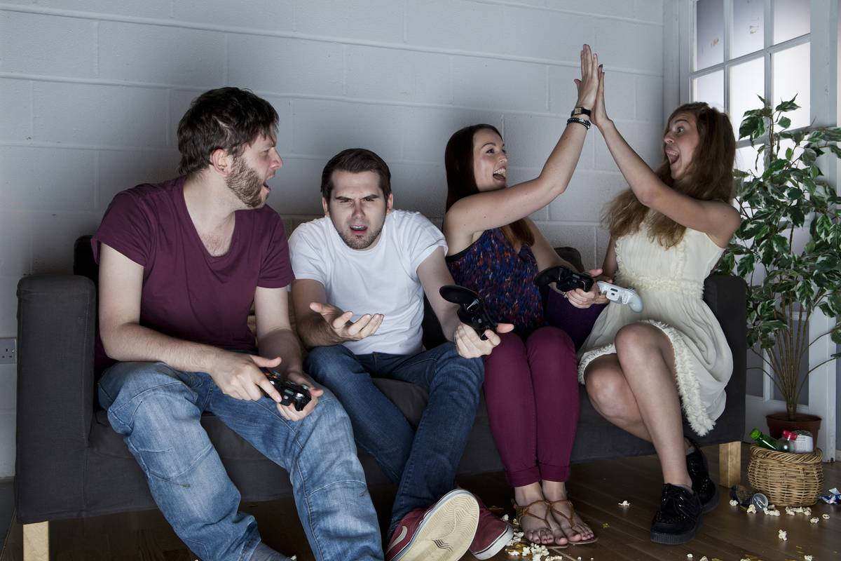 A group of young men and women with various expressions of happiness, anger and confusion playing video games on a sofa