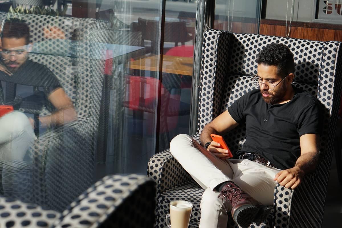 Man sitting on sofa chair using smartphone