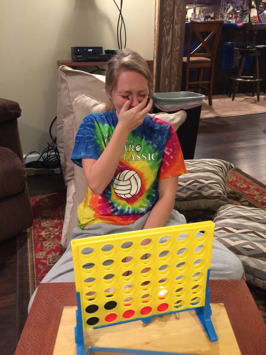 woman crying in front of connect 4 game