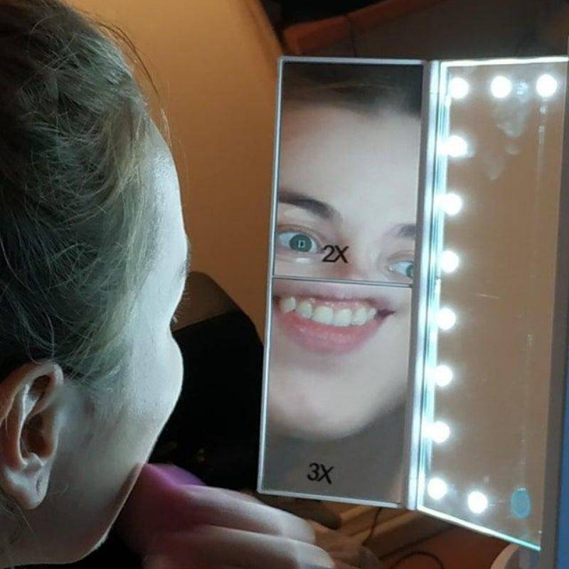 a picture of a girl looking in her makeup mirror