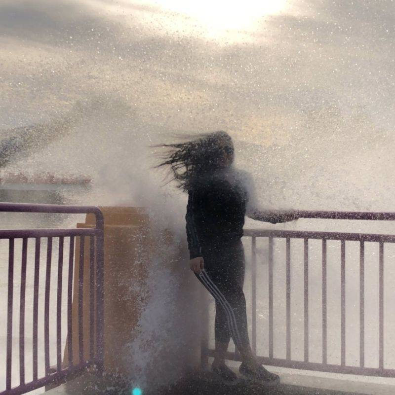 a wave splashing someone trying to take a picture