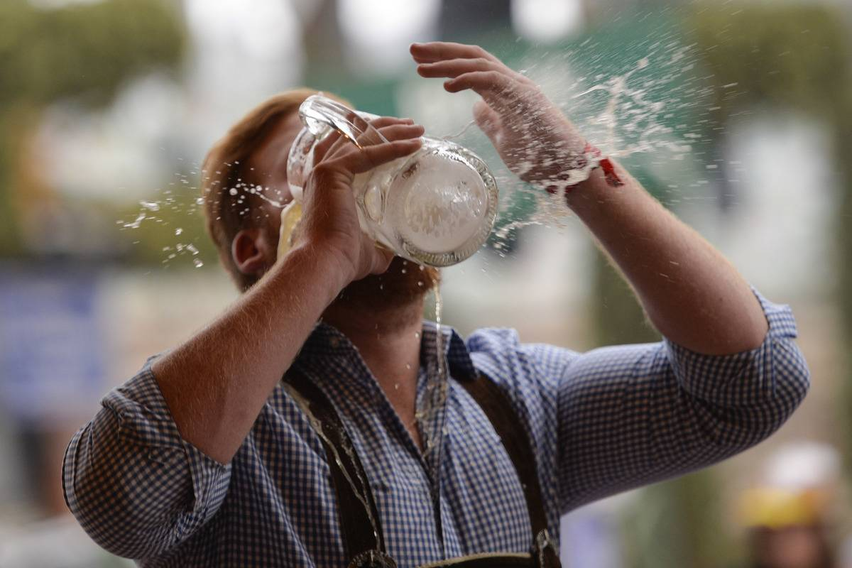 A reveller spills beer as he tries to empty his stein in one sitting