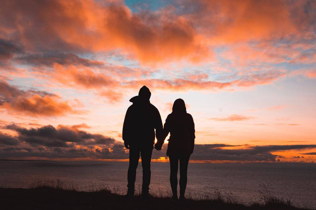 a couple standing in front of a sunset
