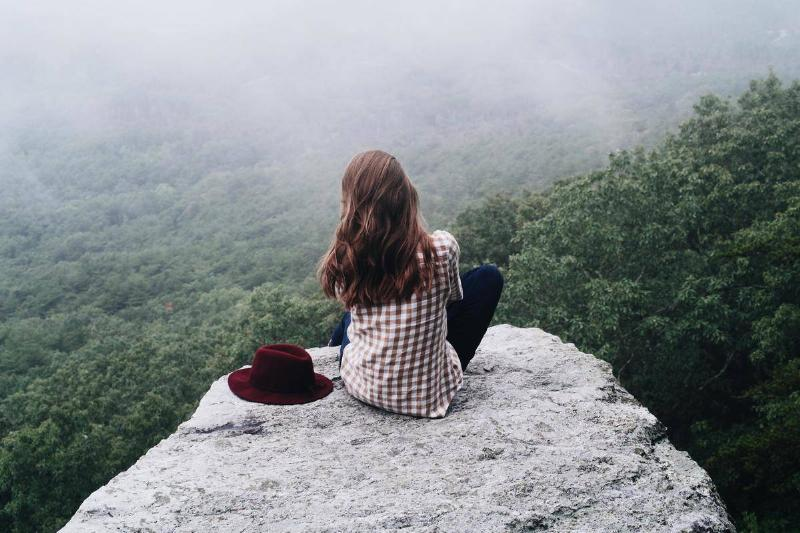 woman sitting on cliff alone