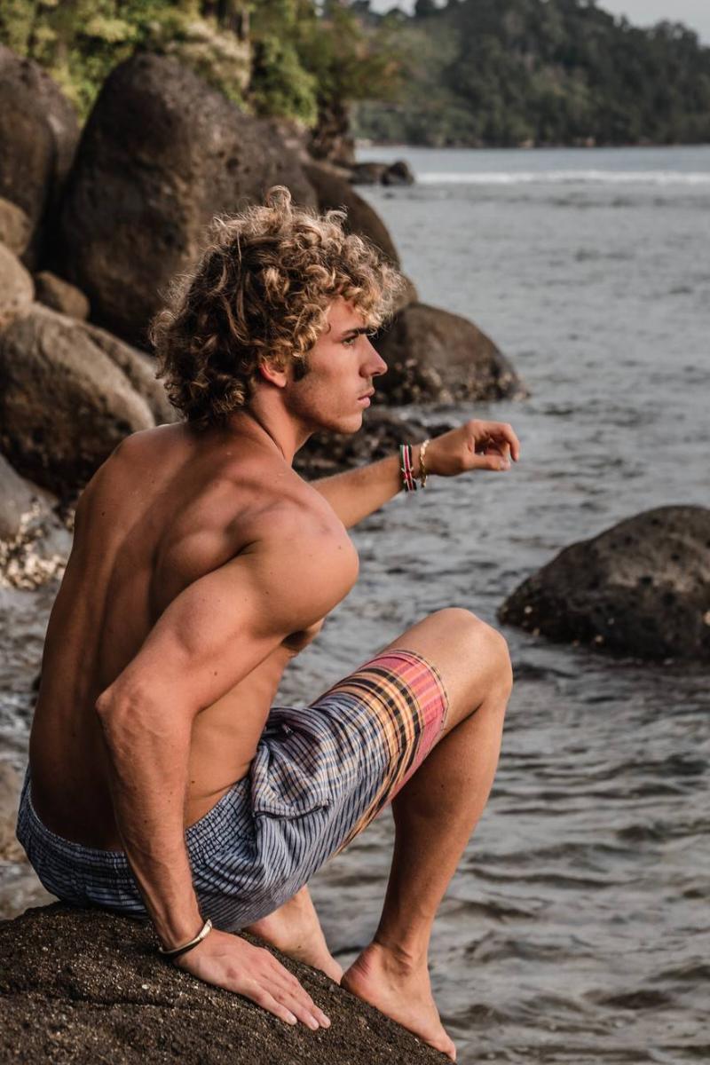 Man sitting on rock by beach