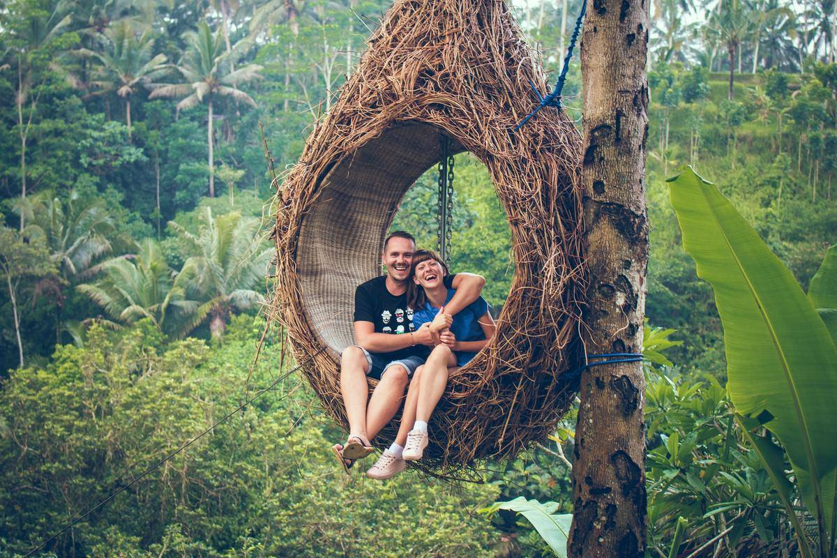 couple swinging from tree