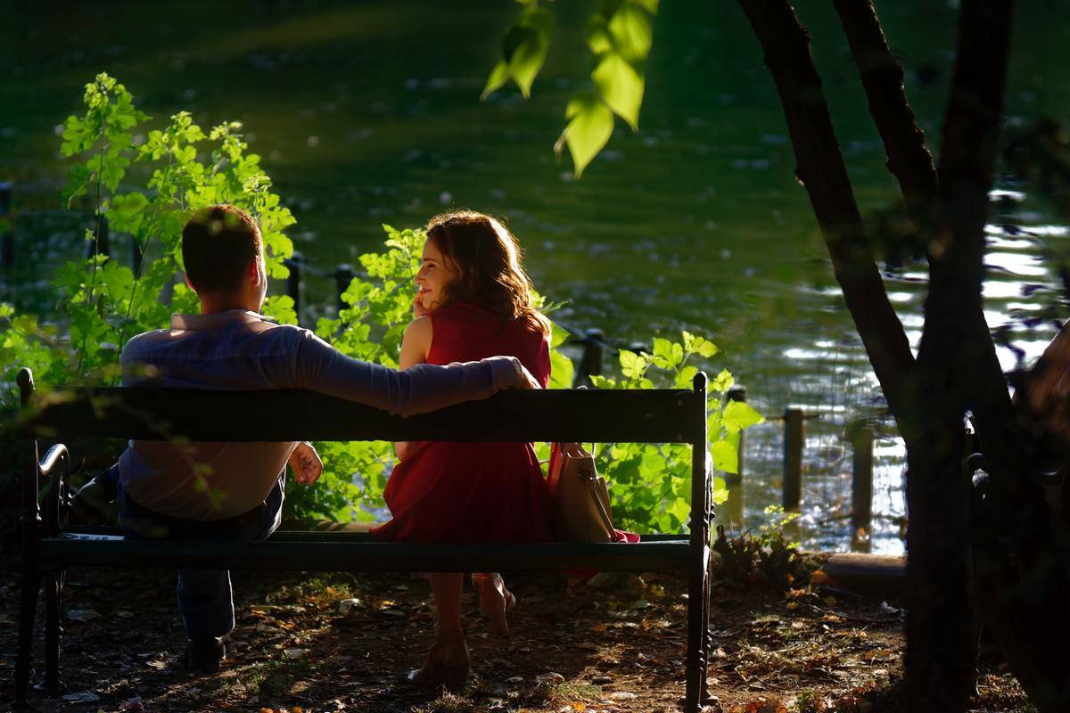 couple sitting outside on bench with greenery around