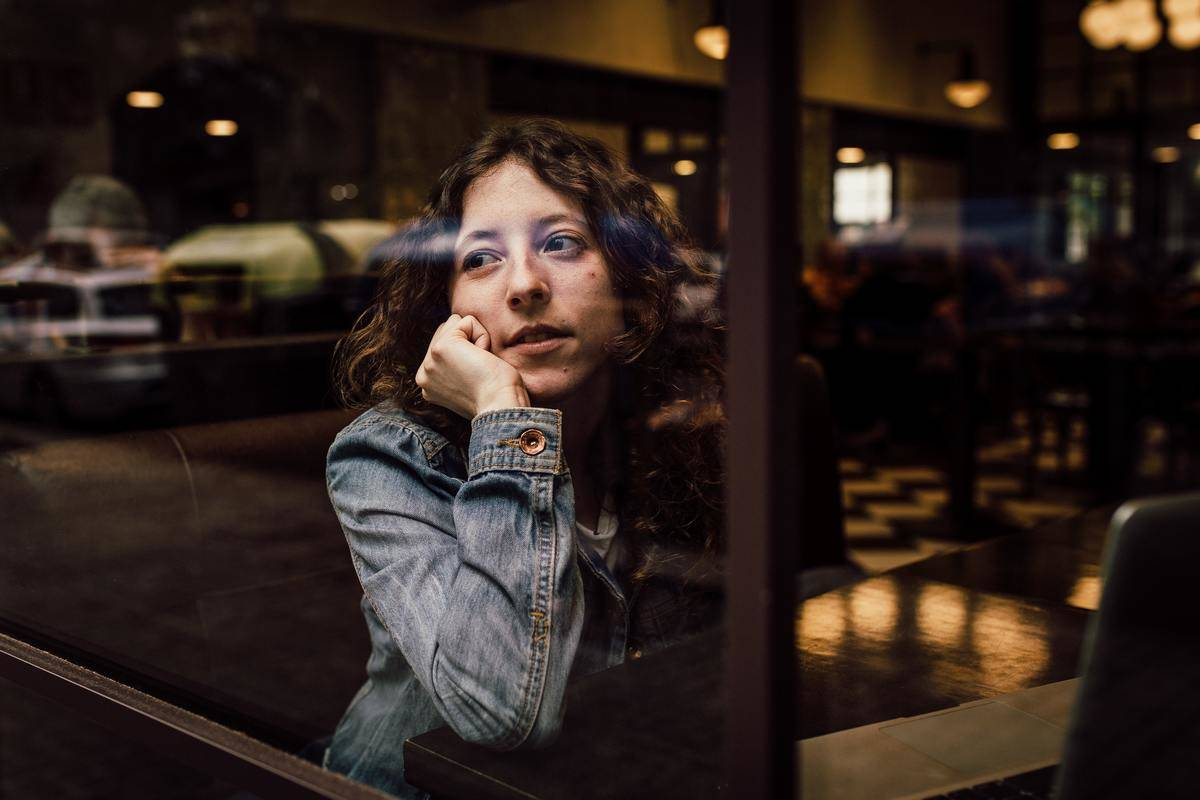 woman looking out window waiting for someone