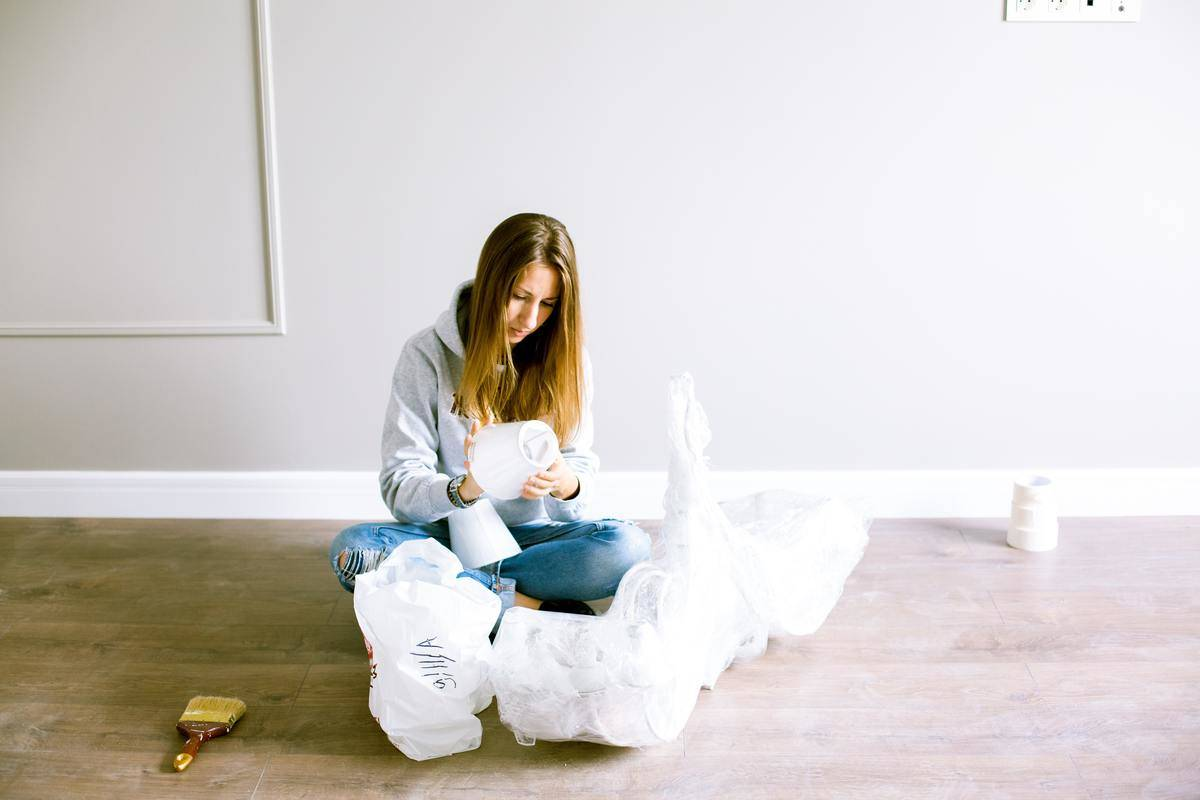woman unpacking in empty apartment