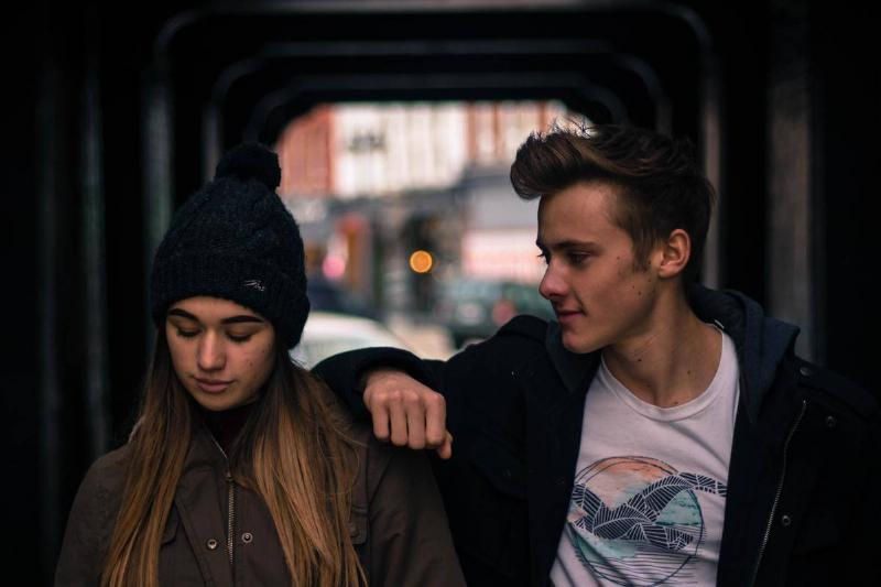man with arm resting on woman looking away outside