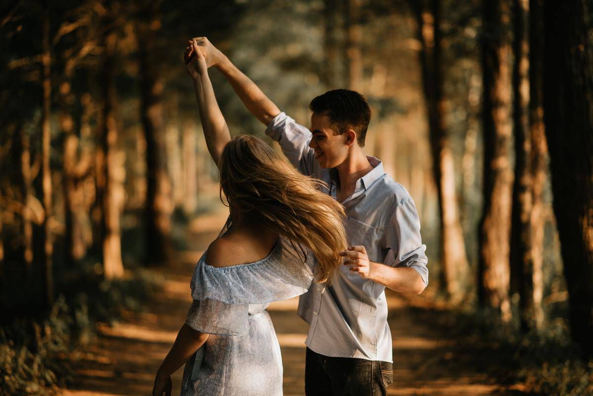 couple mid-spin dancing in the woods