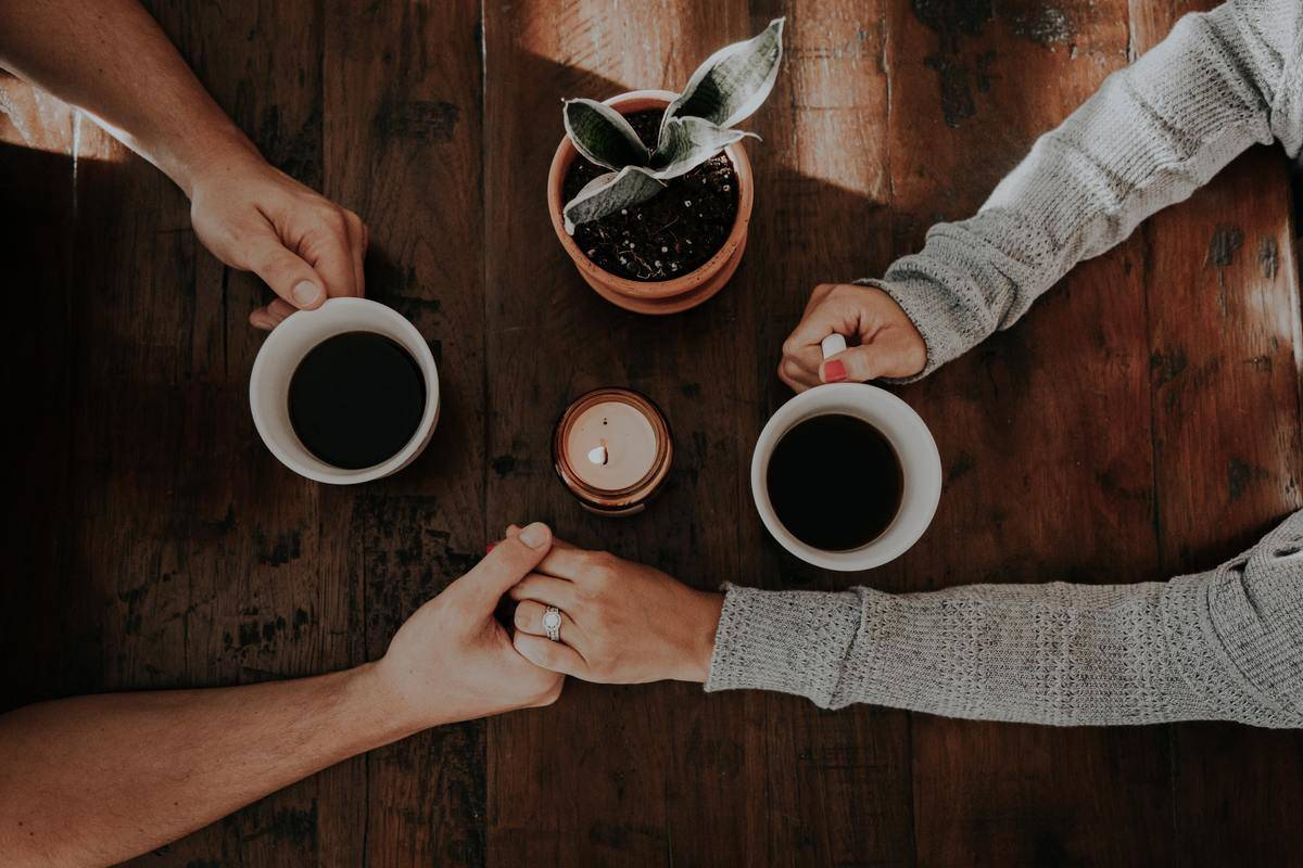 man and woman holding hands while drinking coffee
