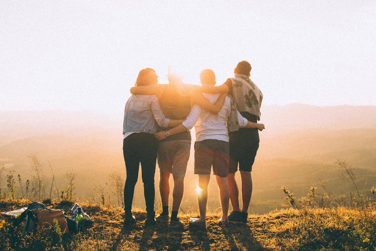 friends embrace by the sunset