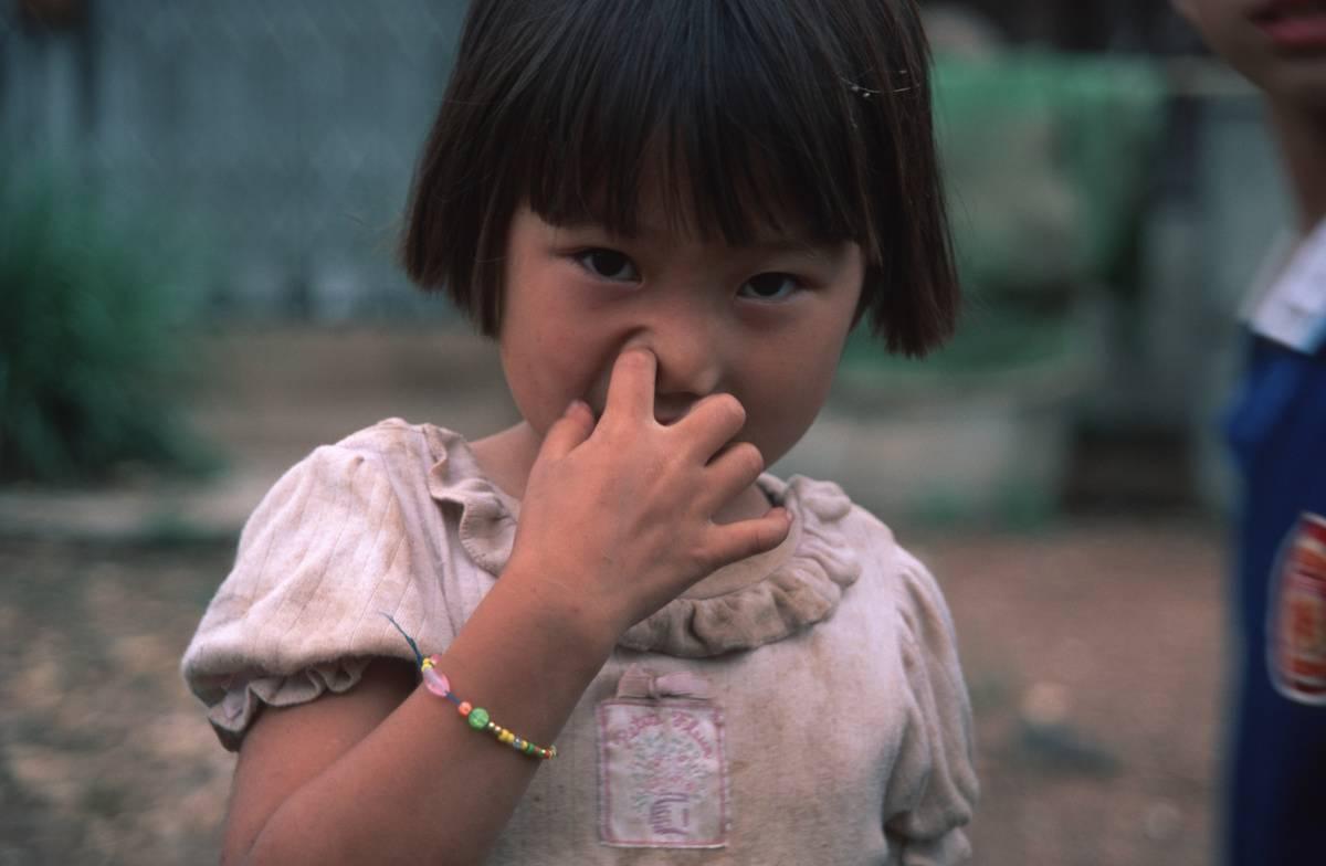 child in thailand picking her nose