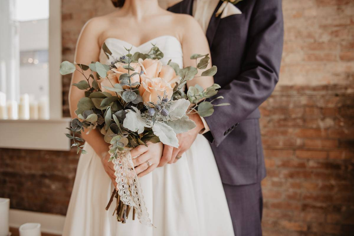 groom holds his bride in front of him as she shows off her bouquet