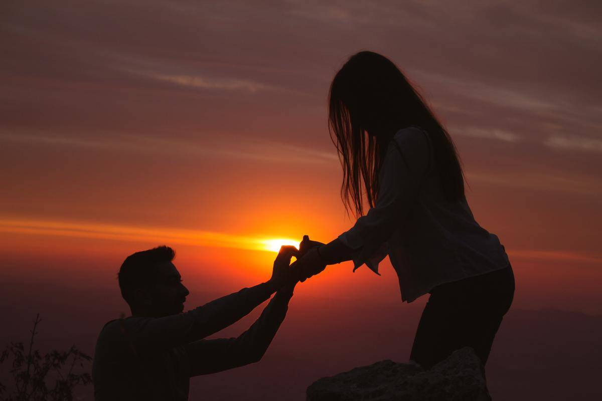 man proposes to woman in the sunset