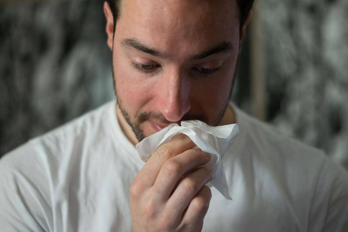 Man is using a tissue to wipe his nose