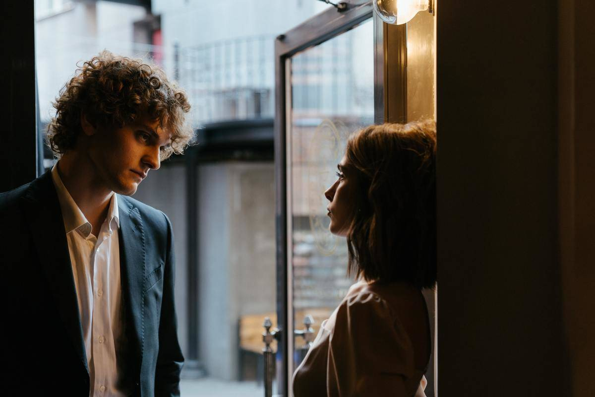 serious couple leaning on doorway