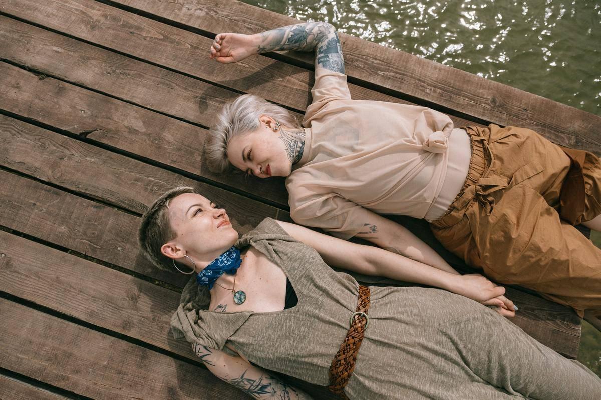 female couple lying on dock