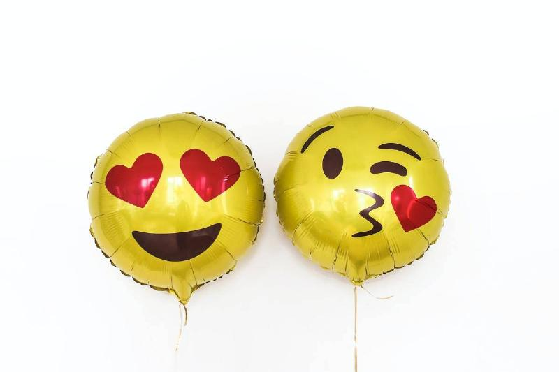 balloons shaped like heart eyes and winky kiss emojis