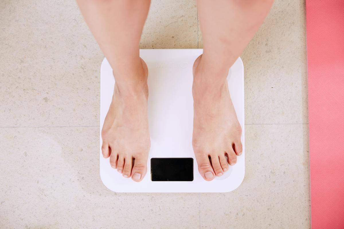 Person weighs themselves on the scale