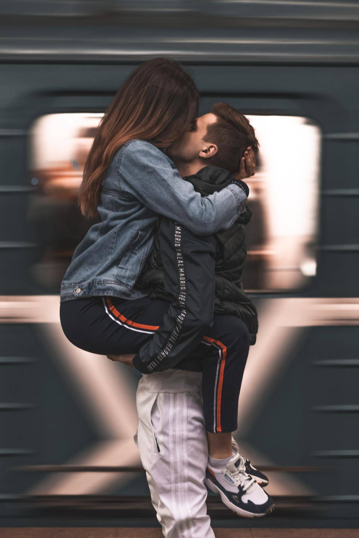couple kissing in front of a moving train