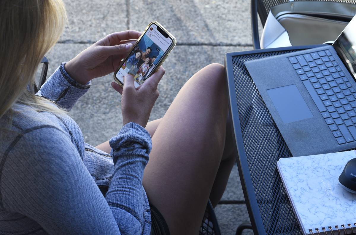 A woman uses her smartphone to look at instagram
