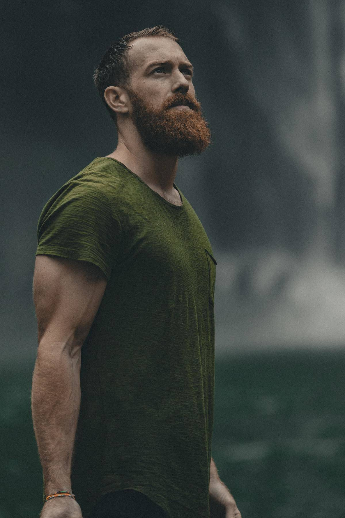 a guy with a beard looking into the distance