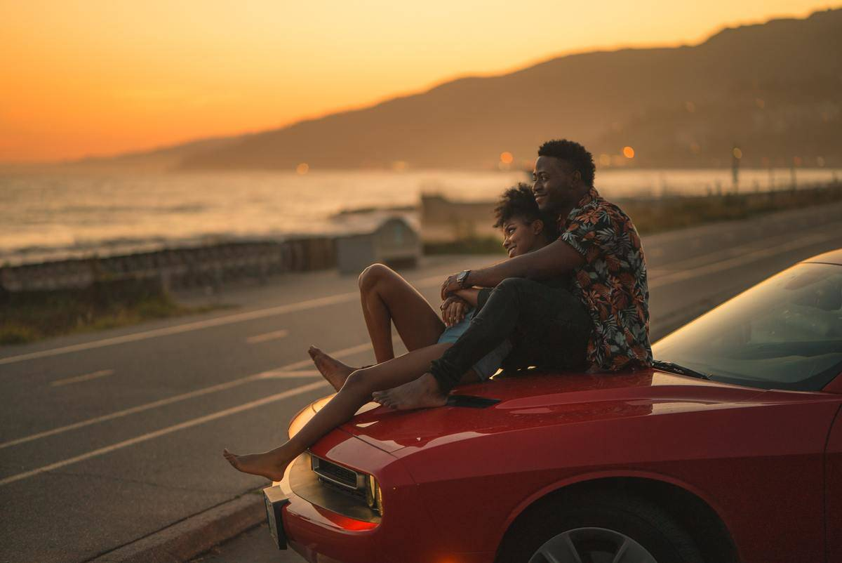 couple sitting on top of a car