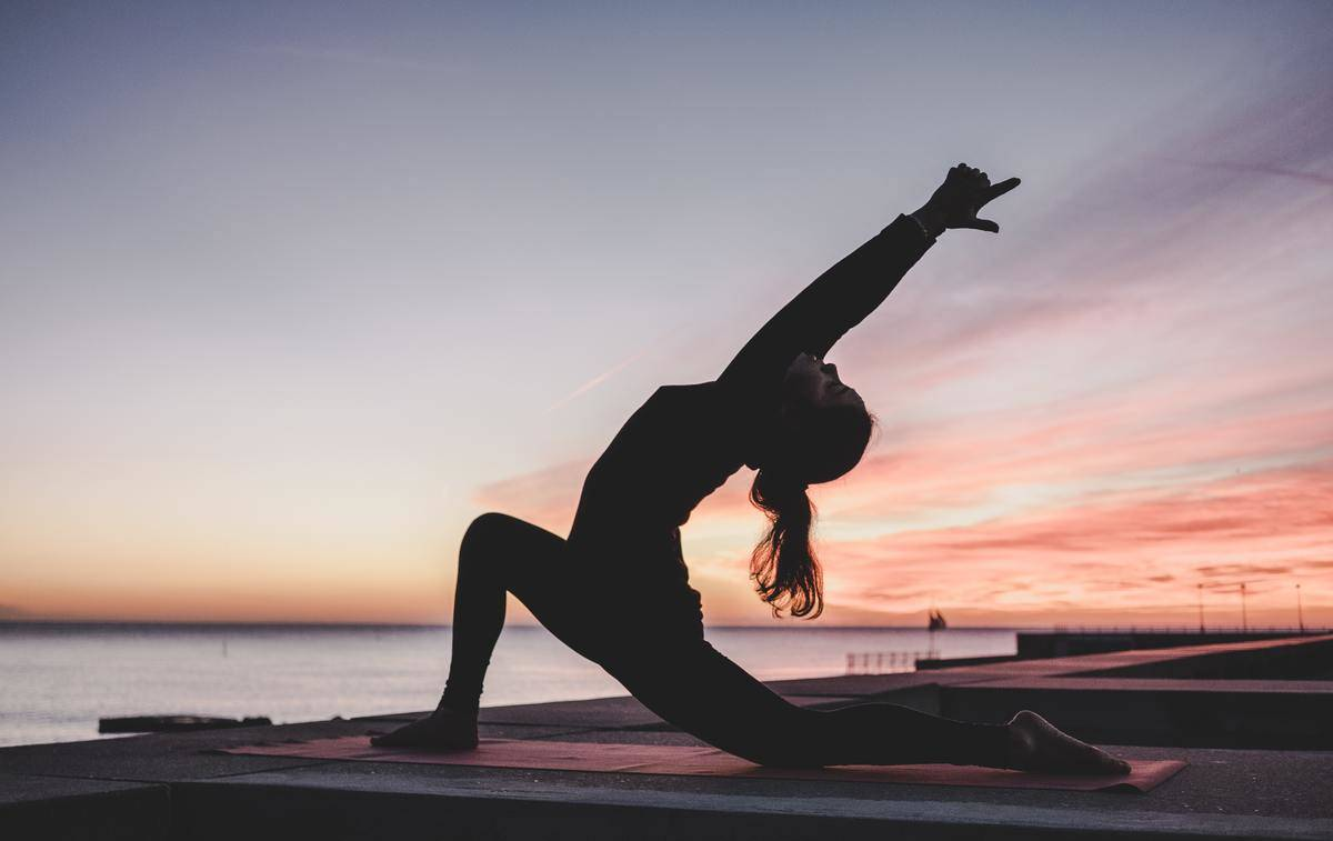 woman doing yoga outside in the sunset