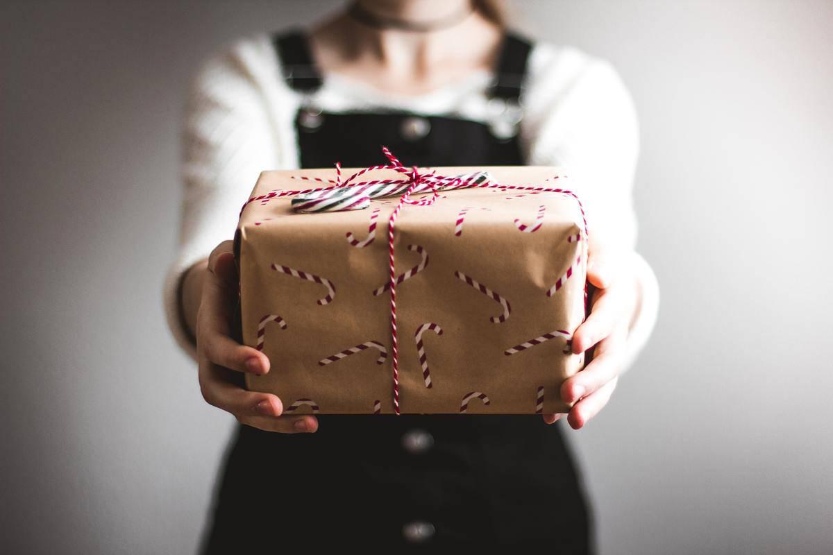 woman handing over christmas present
