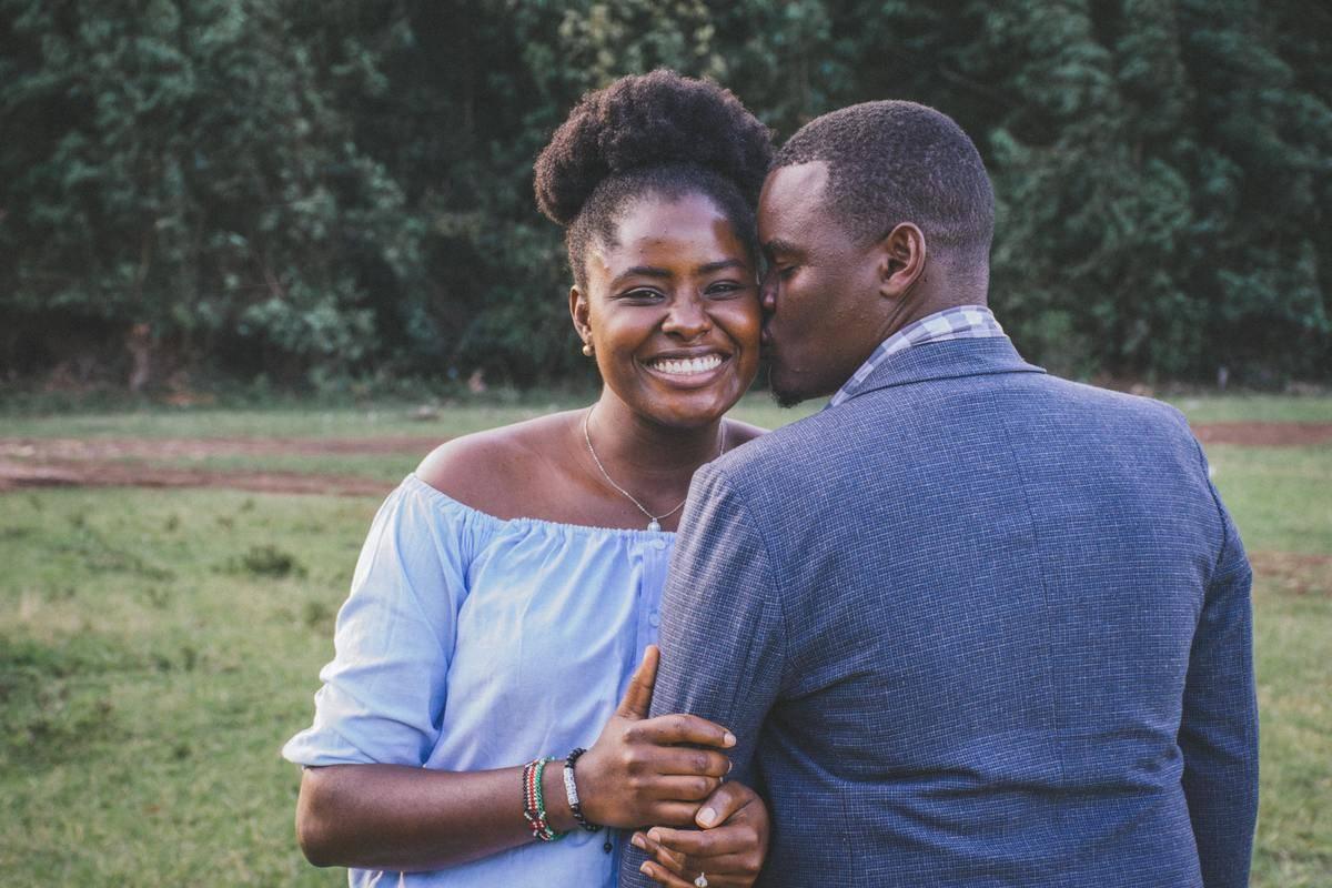 man kissing woman's cheek outside standing