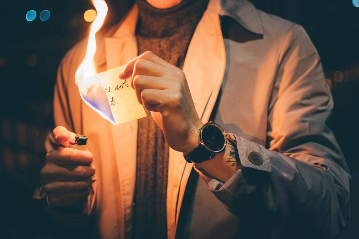 man lighting paper on fire