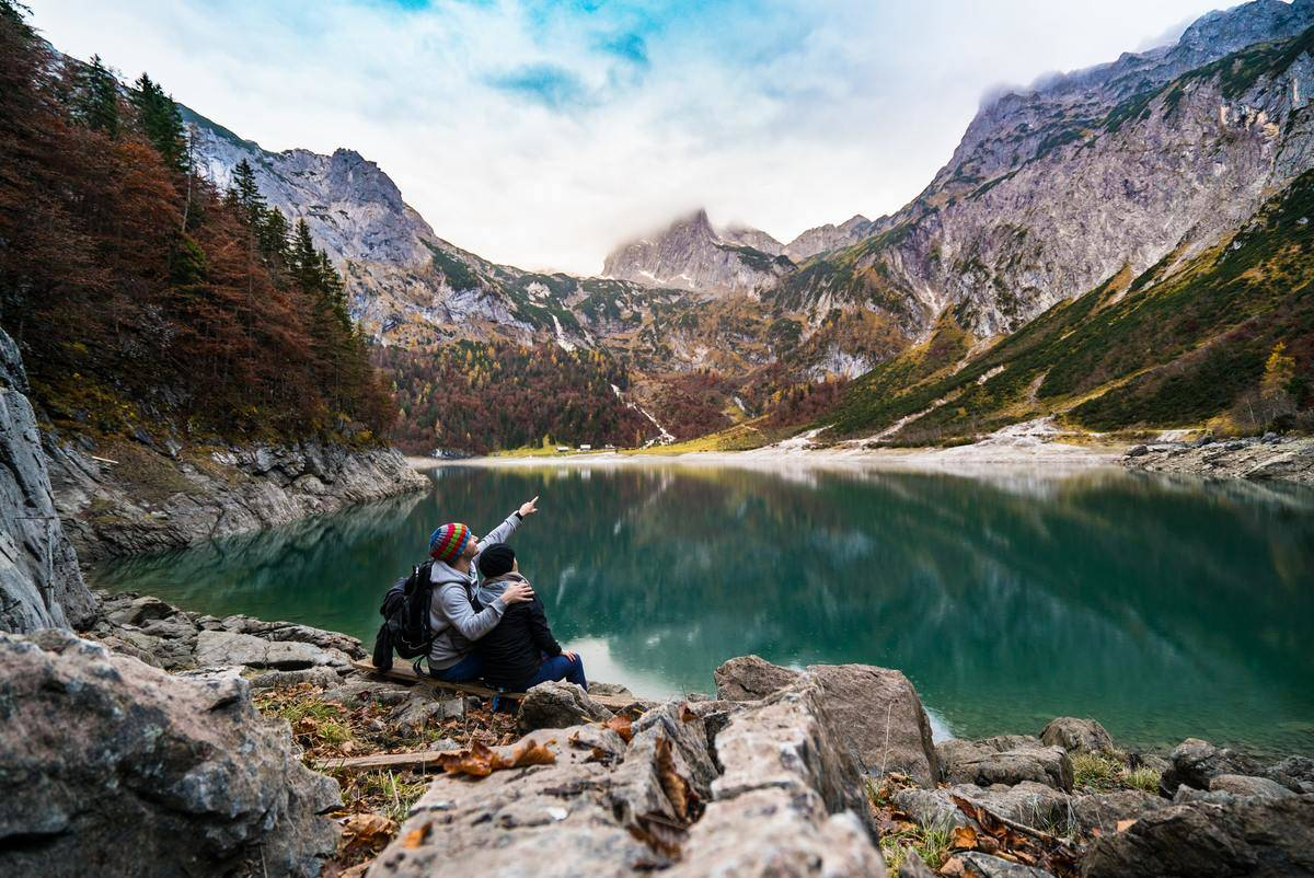 man and woman sitting at edge of mountain lake