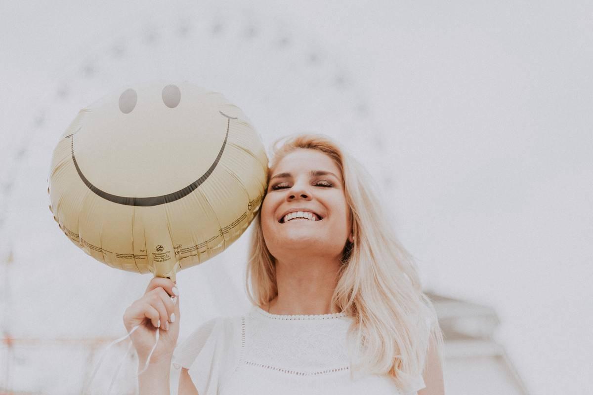Woman smiling holding smily face balloon