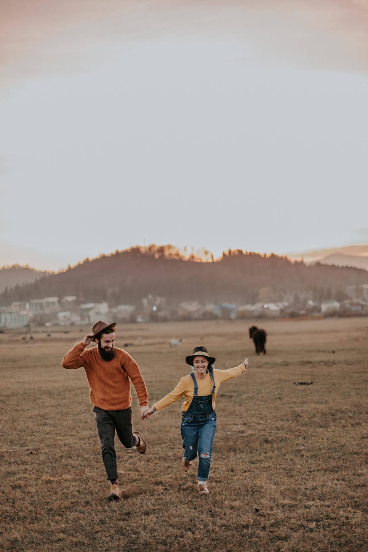 a couple running through a field
