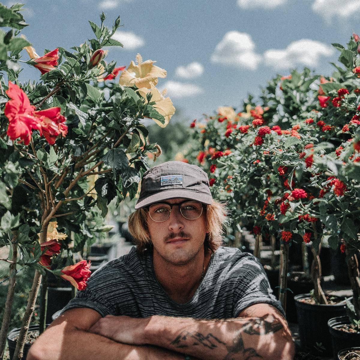 guy sitting around some plants
