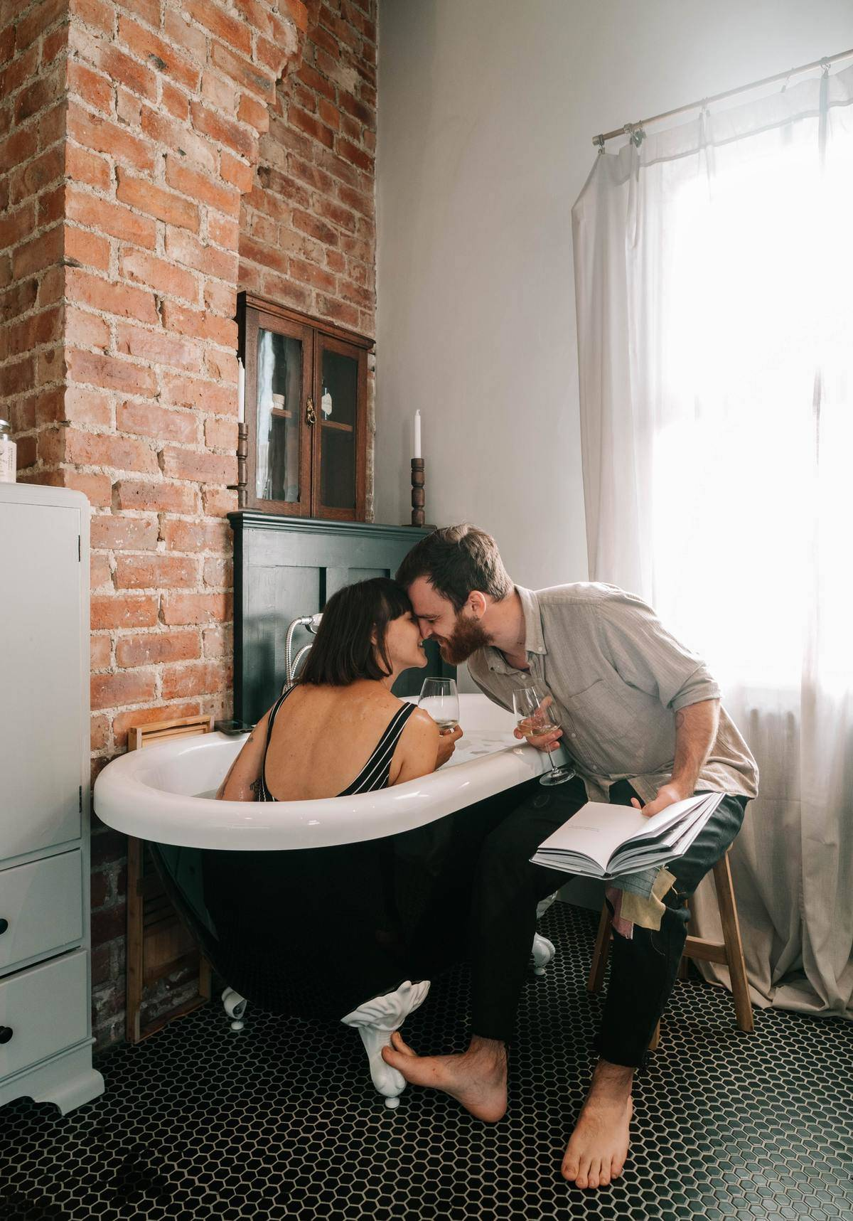 guy reading to girlfriend who is in the tub