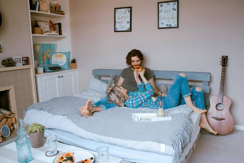 couple eating pizza on a bed