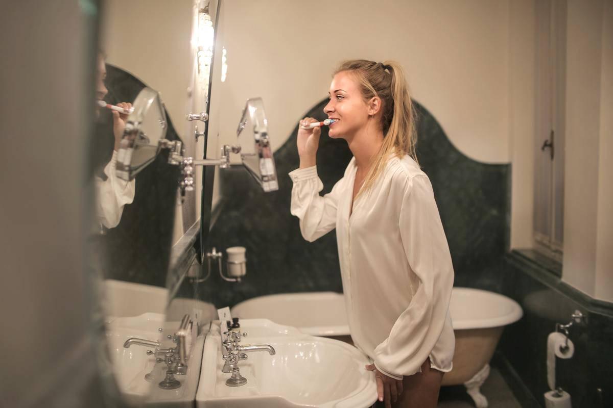 woman rbushing teeth in mirror