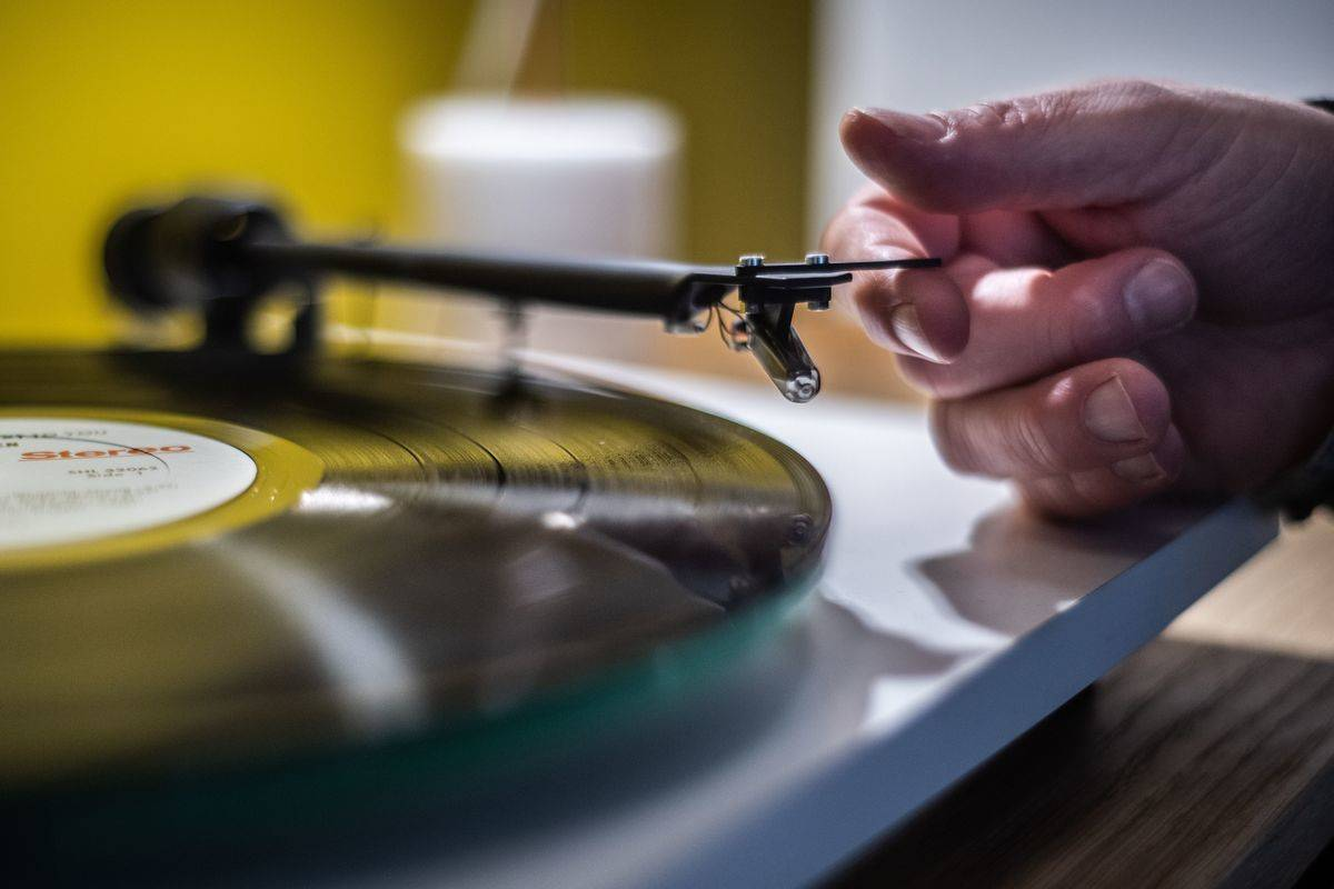 A man playing a turntable vinyl record player in a music store