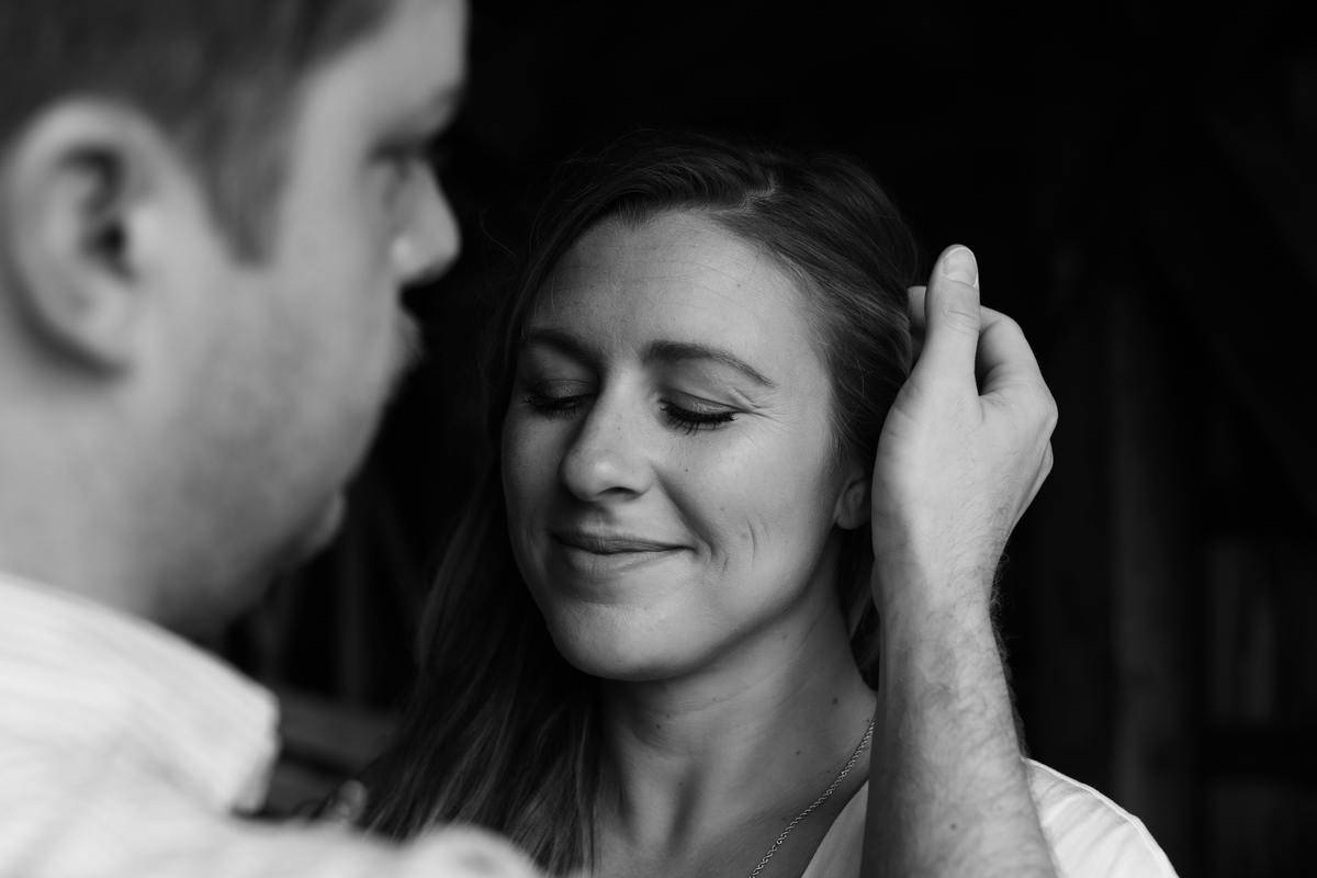 man brushing womans hair out of face smiling
