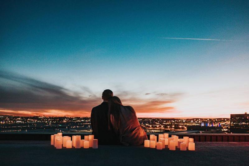 couple looks over sunset with candles