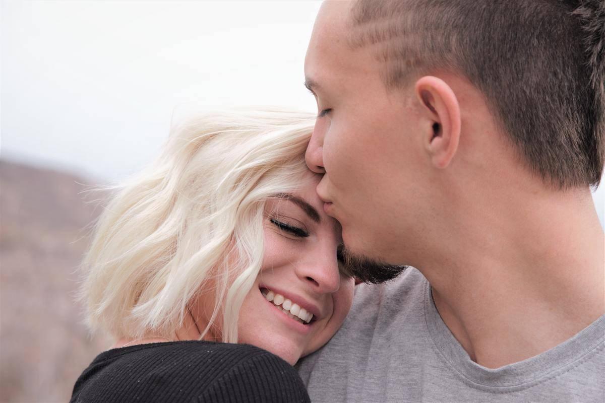 man kisses woman on the cheek