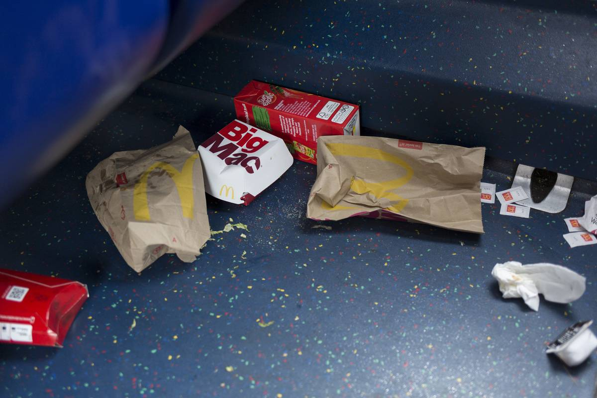 Dropped McDonalds packaging and food remains on the floor of a London bus
